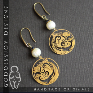 Earrings with brass whale filigree charms, topped with a glowing white cultured pearl, hanging from sleek smooth brass ear wires